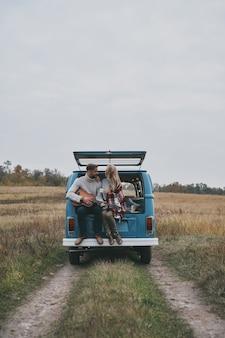 Beste reise. hübscher junger mann, der gitarre für seine schöne freundin spielt, während er im kofferraum des blauen minivans im retro-stil sitzt