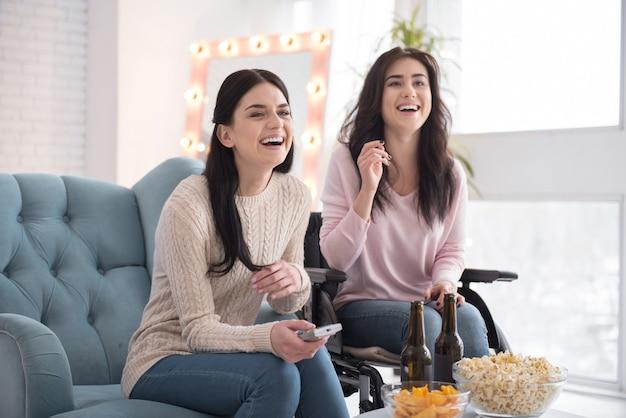 Beste schwestern. aktive schwester und behinderte frau in bezug auf film und lachen Premium Fotos