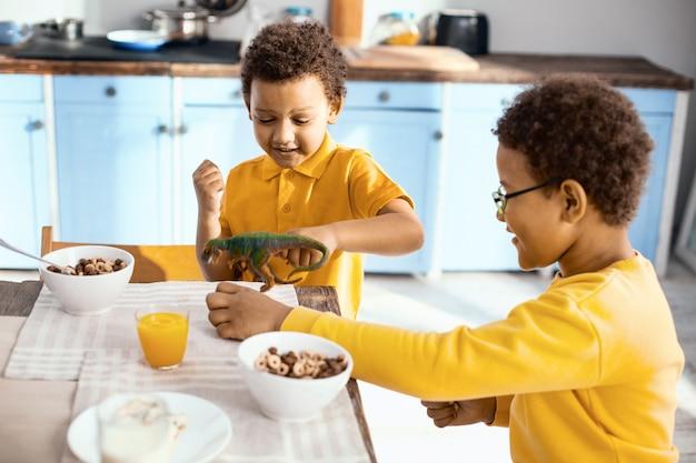 Beste spielpartner. charmante kleine kinder, die am küchentisch sitzen und mit einem spielzeugdinosaurier spielen, während sie frühstücken