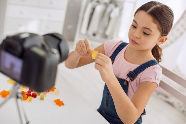 Beste süßigkeiten. angenehmes fröhliches mädchen, das einen der gummibärchen streckt, während es einen videoblog aufzeichnet und verschiedene marken von gummibärchen darin vergleicht
