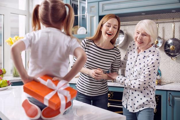 Beste überraschung. charmante junge frau und ihre ältere mutter versuchen zu erraten, was für ein geschenk ihre kleine tochter hinter ihrem rücken versteckt, während sie auf der theke sitzt
