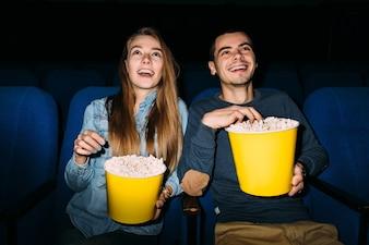 Beste Unterhaltung im Kino. Junge Paare, die einen Film am Kino genießen