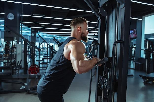 Beste wahl. junge muskulöse kaukasische sportler trainieren im fitnessstudio, machen kraftübungen, üben, arbeiten mit gewichten und langhantel an seinem oberkörper. fitness, wellness, gesunder lebensstil konzept.