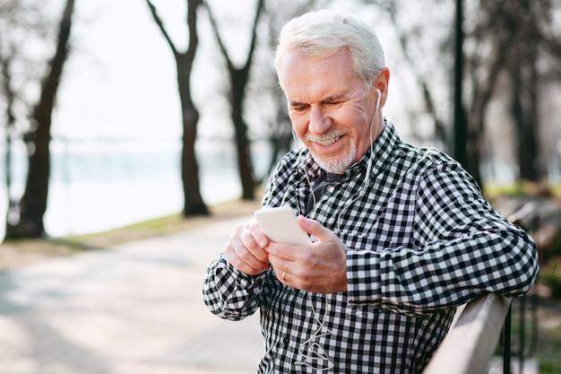 Beste wiedergabeliste. gemütlicher älterer mann, der kopfhörer trägt und musik hört