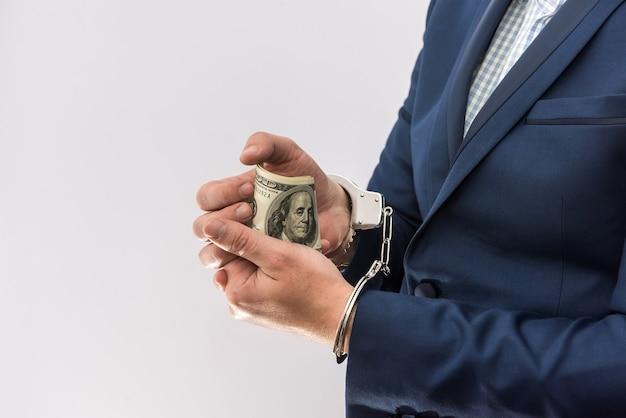 Bestechung und korruption sind der mann, der dollar in der handschelle hält, isoliert. kriminalität