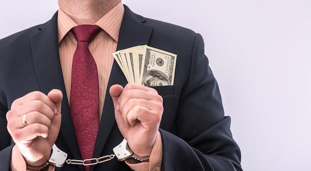 Bestechung und korruption sind der mann, der dollar in der handschelle hält, isoliert