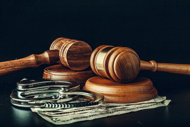 Bestechungsgeld-konzept. dollarbanknoten, -handschellen und -hammer auf tabelle des dunklen schwarzen