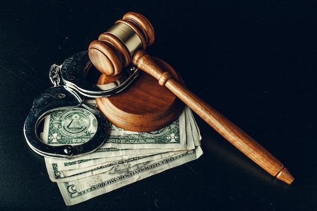 Bestechungskonzept. dollar banknoten, handschellen und hammer auf dunkelschwarzem tisch