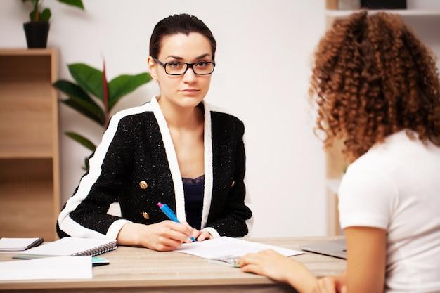 Bestechungskonzept: eine frau gibt einem mitarbeiter des unternehmens ein bestechungsgeld für die unterzeichnung eines vertrags.