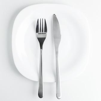 Besteck, gabel und messer auf einer leeren weißen platte auf einem weißen backg