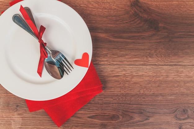 Besteck platte mit einer roten schleife und ein herz