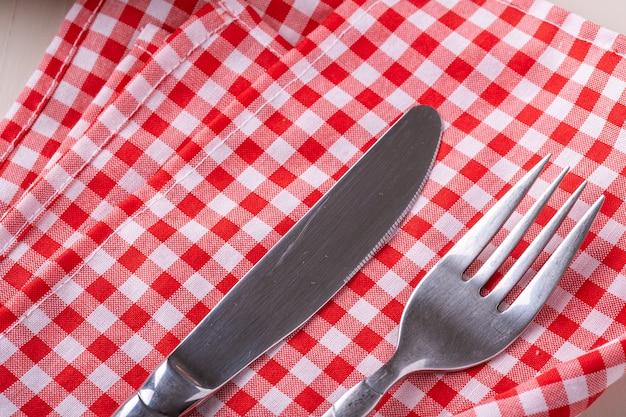 Besteck tischgabel und messer auf roter tischdecke, makro