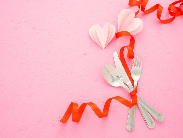 Besteck und herzen auf rosa tisch