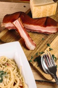 Besteck und pasta in der nähe von fleisch und käse