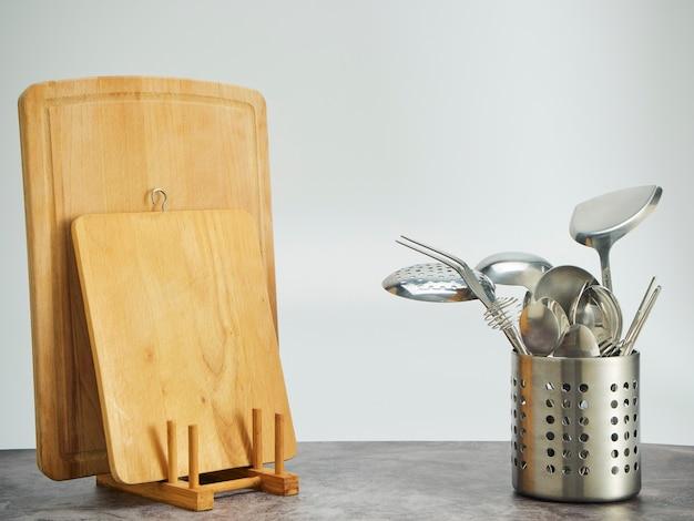 Besteckhalter, schneidebretter aus edelstahl und holz auf dem tisch