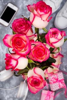 Bestehend aus den rosen und dem handy auf der rückseite eines undeutlichen hintergrunds