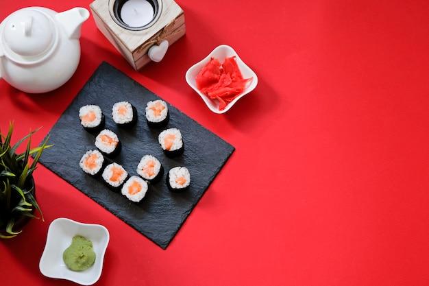 Bestellen sie die lieferung japanischer sushi-rollen, während sie in quarantäne zu hause bleiben. hausform auf rotem hintergrund mit kopienraum