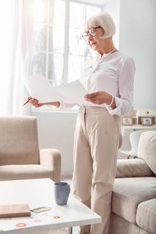Bester analyst. fröhliche ältere frau in einem noblen outfit, die in ihrem wohnzimmer steht und forschungsdaten auf den ausdrucken vergleicht