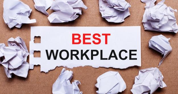 Bester arbeitsplatz geschrieben auf weißem papier auf einem hellbraunen hintergrund.