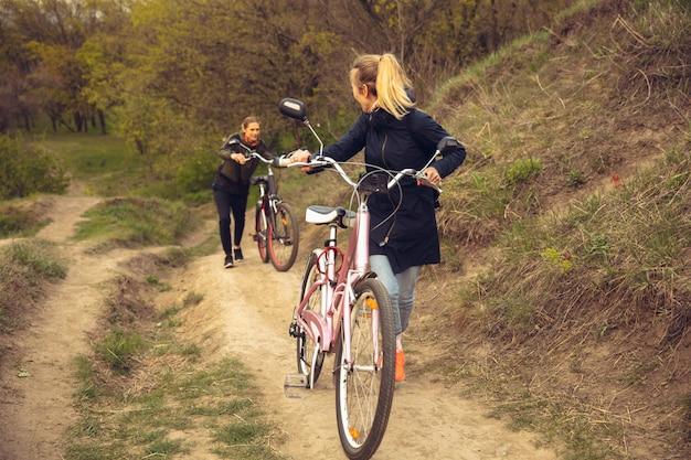 Bester freund, der spaß in der nähe des landschaftsparks am meer hat und fahrrad fährt
