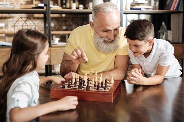 Bester lehrer. fürsorglicher lächelnder großvater, der einen bauern hält und seinen geliebten enkelkindern die schachregeln erklärt, während sie ihm aufmerksam zuhören