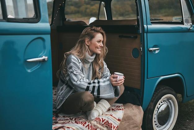 Bester ort zum ausruhen. attraktive junge lächelnde frau, die einen becher hält und weg schaut, während sie innerhalb des blauen retro-art-minivans sitzt