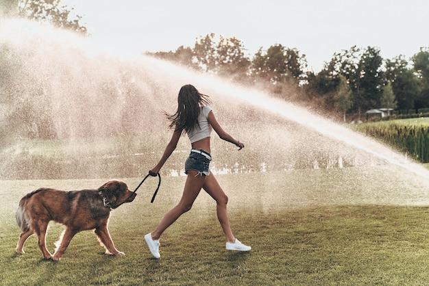 Bester tag überhaupt! in voller länge der schönen jungen frau, die mit ihrem hund beim laufen im freien spielt