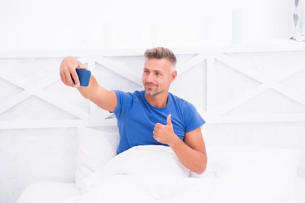 Bester tag überhaupt. kerl, der internet genießt. social-media-sucht. handysüchtiger. flirten und sms senden. häuslicher lebensstil mit mobilem missbrauch. gut aussehender mann, der selfie macht. entspannter mann im schlafzimmer.