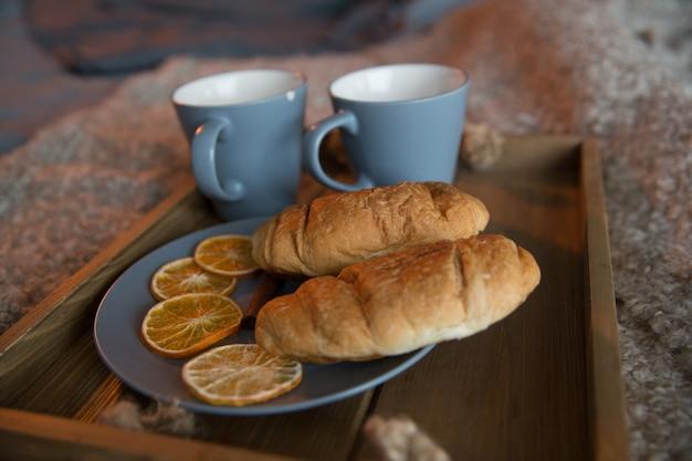 Bestes croissant, croissant, einfaches croissant mit schwarzem tee in einer blauen tasse, leckeres frühstück für jeden tag