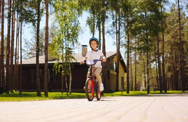 Bestes fahrrad aller zeiten. üppiger kluger junge, der lächelt und sein modernes fahrrad fährt