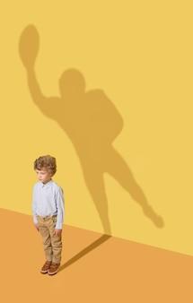 Bestes mitglied des teams. kindheits- und traumkonzept. konzeptbild mit kind und schatten auf der gelben studiowand. kleiner junge will american-football-spieler werden und eine sportkarriere aufbauen.
