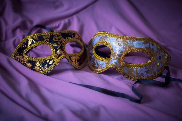 Bestickte masken mit purpurrotem vorhang für karnevalshintergrund