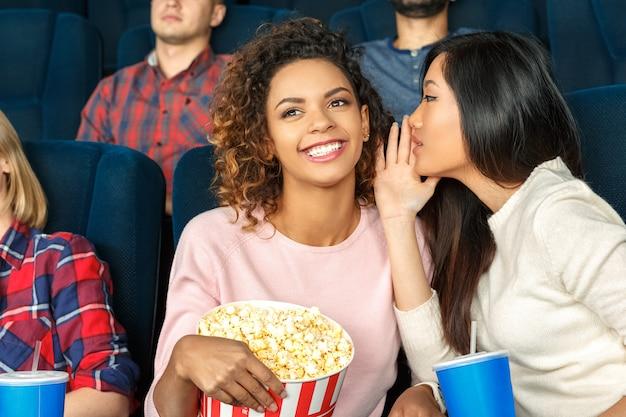 Besties qualitätszeit. junge asiatische frau, die zu ihrer herrlichen afrikanischen freundin beim aufpassen von filmen am kino flüstert