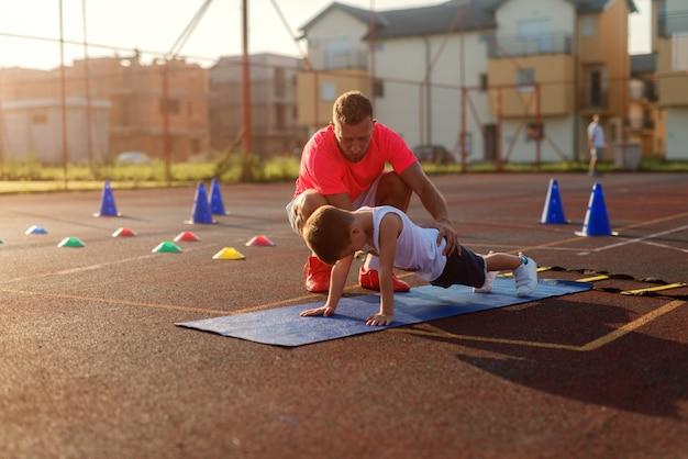 Bestimmender junger fußballtrainer lernt kleinen jungen, wie man liegestütze macht.