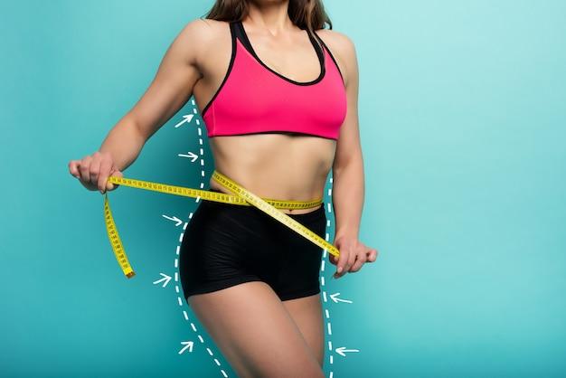 Bestimmte sportfrau hat eine ausgezeichnete körperliche form und misst mit der meter-cyan-oberfläche