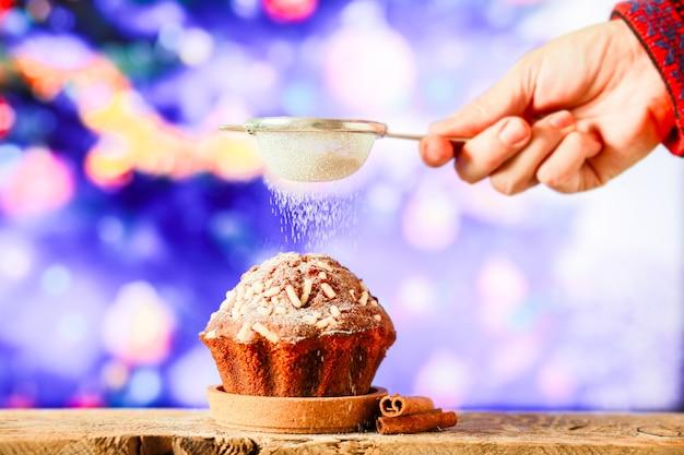 Bestreuen sie den weihnachtscupcake mit puderzucker cupcake auf dem hintergrund eines weihnachtsbaums