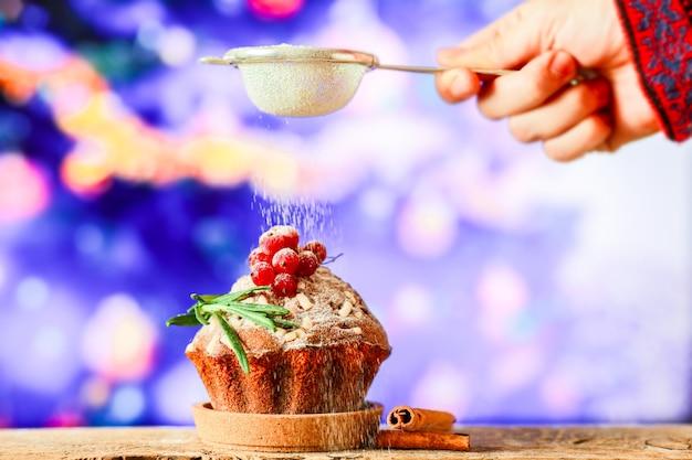 Bestreuen sie den weihnachtscupcake mit puderzucker süße für weihnachten auf dem hintergrund von