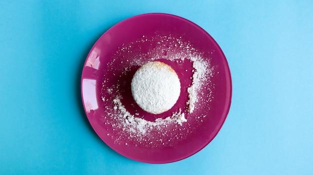Bestreuen sie einen hüttenkäse mit puderzucker auf einem rosa teller auf blauem hintergrund, draufsicht. dessert, ein kleiner cupcake. lebensmittelkonzept. weiße gebackene kekse mit einer luftigen textur. platz kopieren.