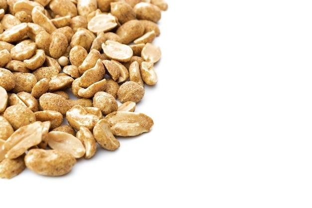 Bestreute nüsse mit schwarzem pfeffer in nahaufnahme auf weißem hintergrund isoliert