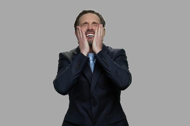 Bestürzter gestresster geschäftsmann auf grauem hintergrund. überforderter depressiver geschäftsmann. insolvenzkonzept.