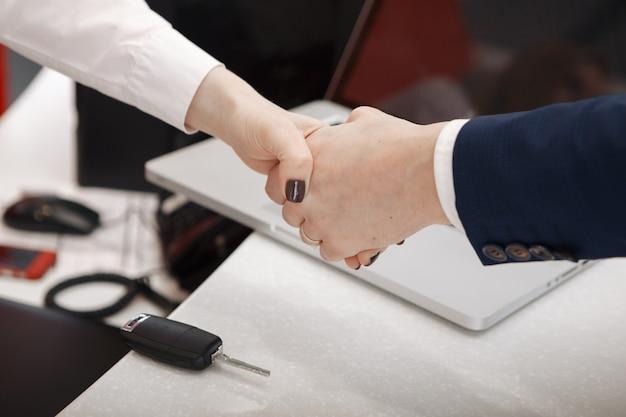 Besuch beim autohaus. männer schütteln sich die hände, während sie dokumente unterschreiben