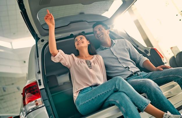Besuch beim autohaus. schönes paar sitzt im offenen kofferraum ihres neuen autos und lächelt.