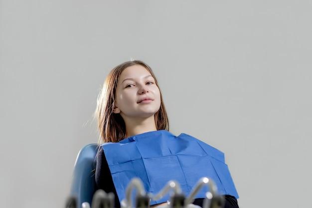 Besuch beim zahnarzt. porträt einer glücklich lächelnden patientin, die im zahnarztstuhl sitzt