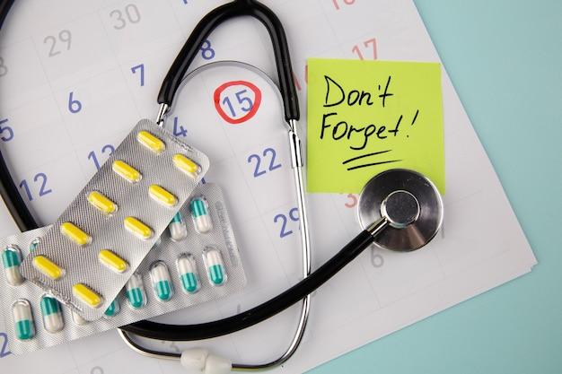 Besuchen sie the doctor reminder auf haftnotiz, pillen und stethoskop in einem kalender.