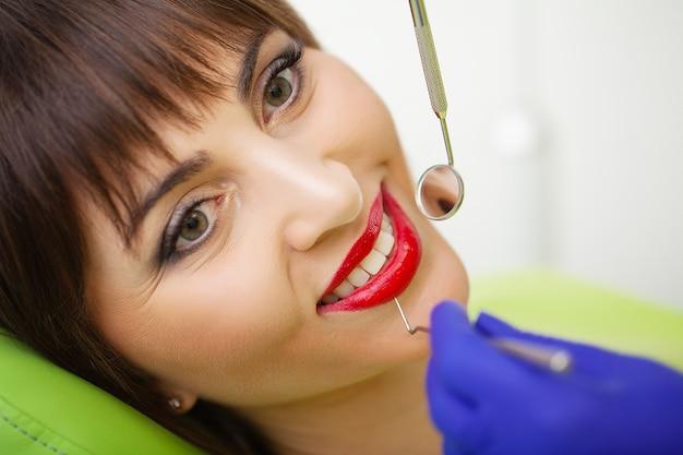 Besuchszahnarztbüro des jungen weiblichen patienten. frau, die zähne an den zahnärzten überprüfen lässt