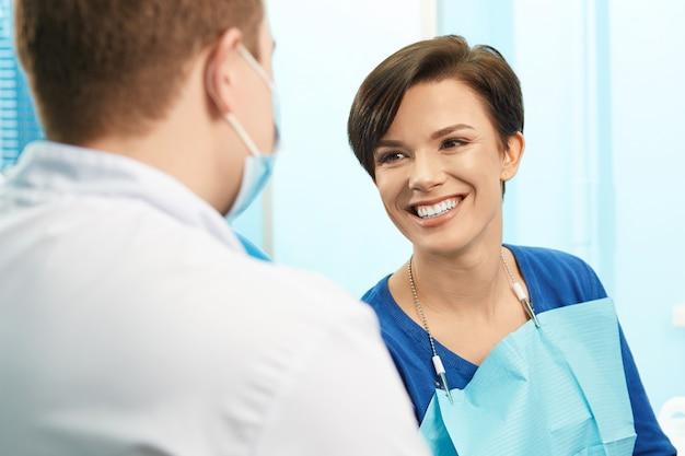 Besuchszahnarztbüro des jungen weiblichen patienten. schöne lächelnde frau mit den gesunden geraden weißen zähnen, die am zahnmedizinischen stuhl sitzen. zahnarztklinik. stomatologie