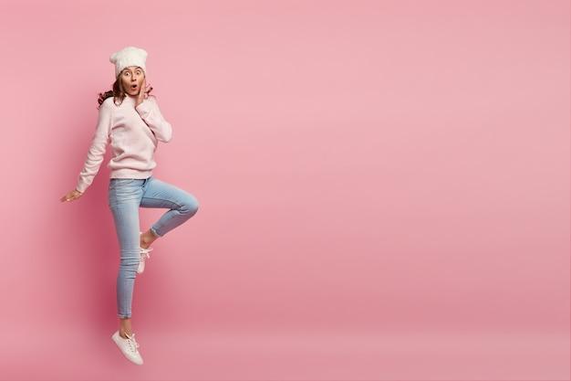Betäubte junge europäische frau mit lockigem haar, trägt stilvolle kleidung