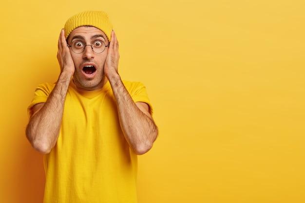 Betäubter emotionaler europäischer mann hält die hände im gesicht, den mund weit geöffnet, kann nicht an schockierende relevanz glauben, trägt leuchtend gelbe kleidung und ist sehr emotional. omg-konzept