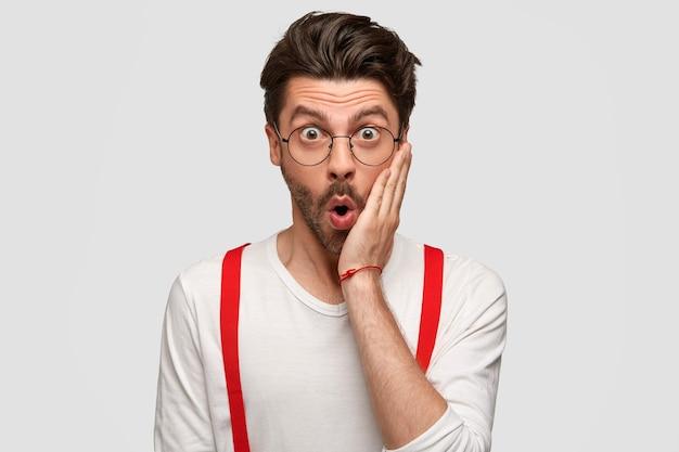 Betäubter emotionaler mann berührt die wange, sieht verwirrt aus und starrt mit verwanzten augen