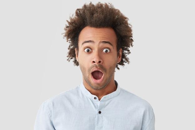 Betäubter hübscher junger mann mit buschigem dunklem haar, hält den kiefer gesenkt, öffnet die augen weit, kann nicht an unglück glauben, drückt große überraschung aus